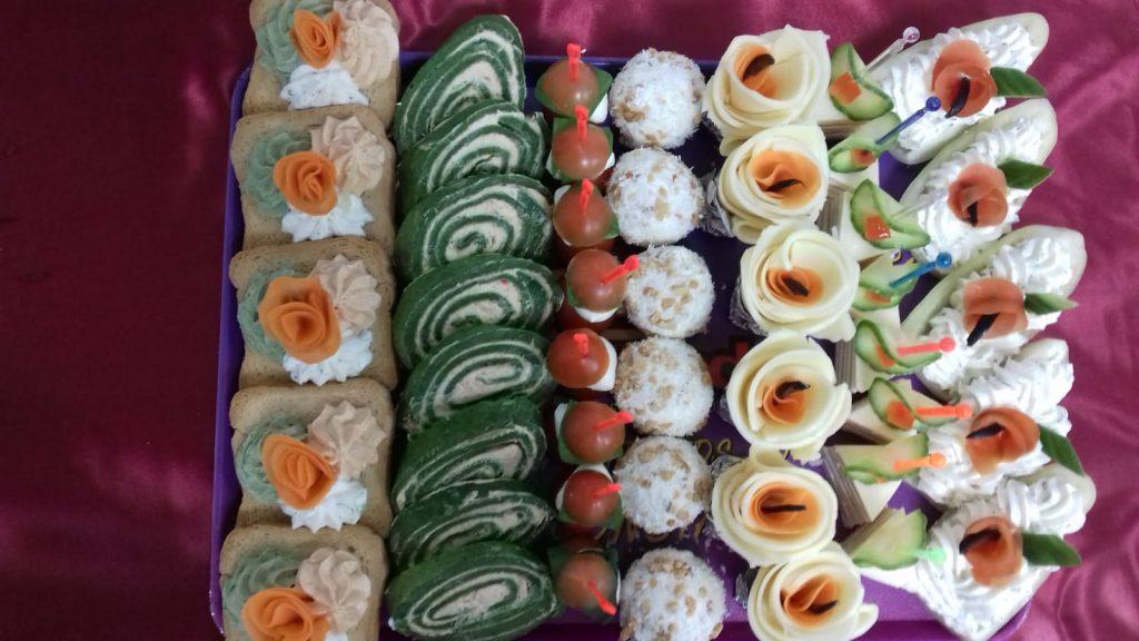 Platou dreptunghiular 09 - contine: tartina cu crema de branza tricolora (5 buc), rulada de spanac cu crema de branza (8 felii), frigarui capresse (8 buc), bile din crema de branza cu alune (6 buc), flori din cascaval (6 buc), dobos (8 buc), barcute din ardei cu crema de branza (5 buc) – Pret 129,99 lei/ buc ;